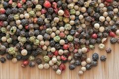 Grain de poivre mélangé sur une table en bois Images stock