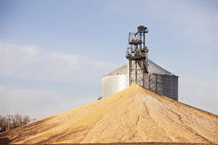 Grain dryer and grain. Grain dryer and immense pile of corn royalty free stock image