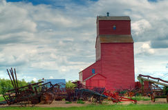 Grain Elevator. A prairie grain elevator shot against a cloudy sky with assorted farm equipoment lying in front - done in HDR Stock Image