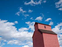 Grain Elevator. Rises into blue sky with clouds Stock Images