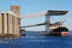 Grain elevator. A grain elevator loading a cargo ship Stock Images