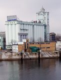Grain elevator. On the river storage of food agriculture farming business huge building Stock Photo