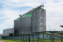 Grain elevator in agricultural zone and solar power station. Royalty Free Stock Photos