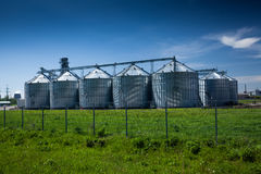 Grain elevator at field against deep blue sky Royalty Free Stock Photo
