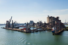 Grain elevator in harbour with terminal and cranes. For transhipment and ships getting loaded Royalty Free Stock Image