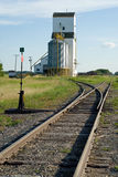 Grain Elevator Near Tracks. A grain elevator situated near a set of railroad tracks with the rails ending in a vanishing point Stock Photos