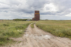 Grain elevator. Old grain elevator with a dirt path leading to it under cloudy skys Stock Photos