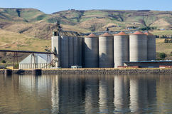Grain elevator storage on river. A grain elevator storage facility on a river Royalty Free Stock Photos