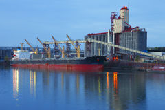 Grain elevators & cargo ship at dusk. Royalty Free Stock Photos