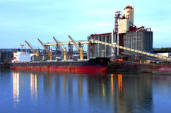 Grain elevators & cargo ship at dusk. Stock Photo