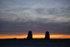 Grain elevators silhouetted against a winter sunset Royalty Free Stock Photo
