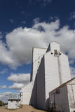 Grain elevators. White grain elevators against a blue sky with clouds Royalty Free Stock Image