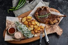 Grain fed Grilled Tomahawk Beef steak with fried potato wedge.  royalty free stock photos