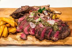 Tomahawk Beef steak. Grain fed Grilled Tomahawk Beef steak with fried potato wedge stock photos