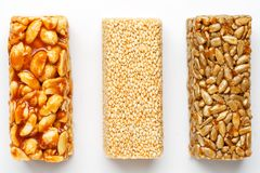 Grain granola bar with peanuts, sesame and seeds in a row on a white background. Top view Three assorted bars, isolate stock photography