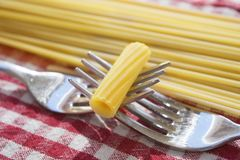 Grain of pasta put between two intertwined forks Royalty Free Stock Photo