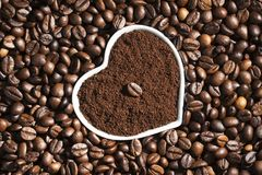 Grain of roasted coffee in a cup in the form of a heart in a pile of coffee beans, background. Stock Photos
