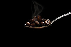 Grain roasted coffee spoon with smoke on black background. Coffee spoon Royalty Free Stock Photography