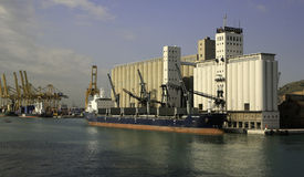 Grain Ship Unloading Grain at Barcelona, Spain. A grain ship unloading gain into a grain elevator in the Barcelona, Spain harbour. Further to the left are Stock Photo