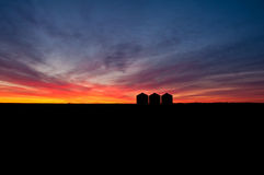 Grain Silo Beauty. Silhouettes of three grain silos during sunrise/sunset in the countryside Stock Image