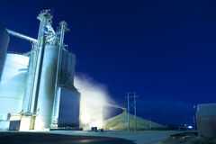 Grain silo at night. Grain silo and dryer at night with pile of grain Stock Photo