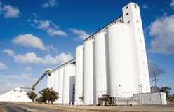 Grain silos for agriculture. Very large grain silos standing tall with beautiful blue sky and clouds in the background Stock Photo