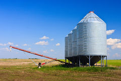 Grain Silos and Auger. Steel grain silos used to store grain along side an auger stock images