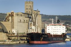 Grain silos and cargo ship at Port of Civitavecchia, Italy, the Port of Rome Royalty Free Stock Image