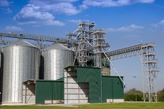 Grain silos. Complex with bright blue sky in the background Stock Photos