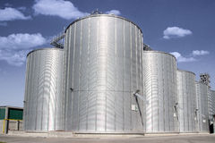 Grain silos. Complex with bright blue sky in the background Royalty Free Stock Photography