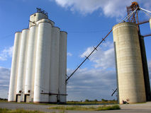 Grain Silos and Elevator. Grain storage silos and elevator stand silently towering over the nearby countryside royalty free stock photo
