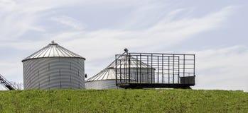 Grain Storage Silos & Farm Wagon. Grain silos glisten in the summers sun near Duanesburg, New York Royalty Free Stock Images