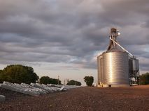 Grain Silos Industry. A collection of steel grain silos in a gravel lot next to the train tracks under a big sky in the late afternoon stock photos