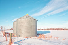 Grain Silos in the Snow. Prairie landscape with fence and grain silos in the snow Stock Images