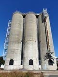 Grain silos. Three storage tall high concrete sunny blue farm farming wheat corn food stock images
