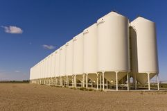 Grain silos under a blue sky. A bank of grain silos sitting on a gravel lot under a deep blue sky with fluffy clouds in Alberta, Canada Stock Photography