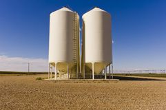 Grain silos under a blue sky. A bank of grain silos sitting on a gravel lot under a deep blue sky with fluffy clouds in Alberta, Canada Royalty Free Stock Photos