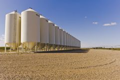 Grain silos under a blue sky. A bank of grain silos sitting on a gravel lot under a deep blue sky with fluffy clouds in Alberta, Canada Royalty Free Stock Image