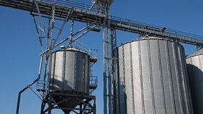 Grain Storage Bins. Steel Grain Silos Agaist the Blue Sky Stock Photography