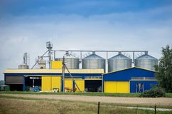 Grain storage. A grain storage with a yellow and blue buildings and steel storage silos under blue skies Royalty Free Stock Photos