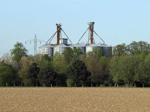 Grain storehouse. Granary behind a row of tree and a field Stock Images