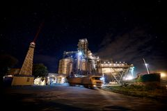 Grain terminal at seaport with starry sky on background. Cereals bulk transshipment from road transport to vessel at. Long exposure photo of big grain terminal Stock Photos