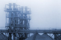 Grain terminal tanks in dense fog, Odessa, Ukraine. Industrial b Royalty Free Stock Photo