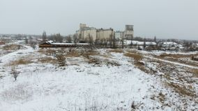 Grain terminal in the winter season. Snow-covered grain elevator in rural areas. A building for drying and storing grain. Grain terminal in the winter season Stock Photo