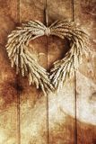Grain Wreath. Decorative grain wreath against a wooden paneled door. Textured grunge layer applied for grunge rustic effect royalty free stock photos