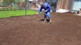 Graine de propagation d'herbe d'homme de paysagiste à la main pour la pelouse parfaite Tir statique banque de vidéos