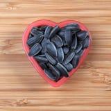 Graine de tournesol dans une cuvette de coeur Photographie stock libre de droits