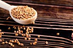 Graines crues de sarrasin dans la cuillère en bois sur la table en bois Eatin sain images libres de droits