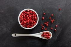 Graines d'épice de poivron rouge dans la cuvette et la cuillère de porcelaine Photo stock