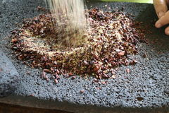 Graines de cacao étant fondues dans un mortier Image stock